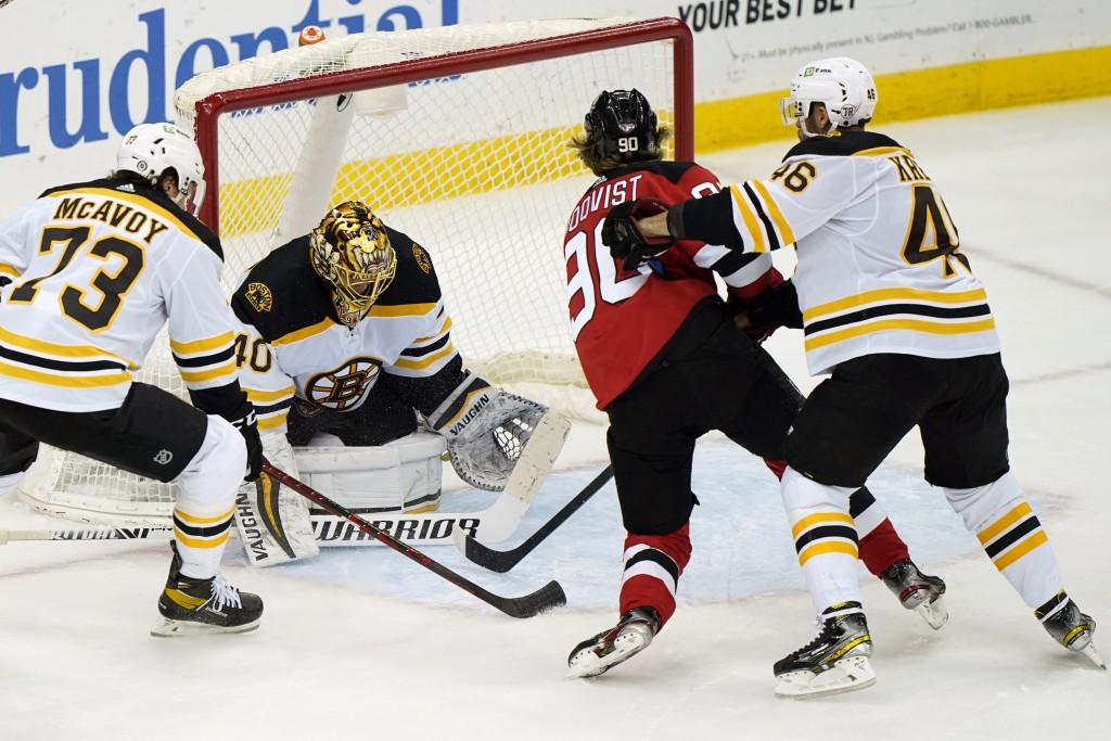 Boston Bruins center David Krejci (46) defends New Jersey Devils center Jesper Boqvist (90) in front of Bruins goaltender Tuukka Rask (40) as Bruins d...