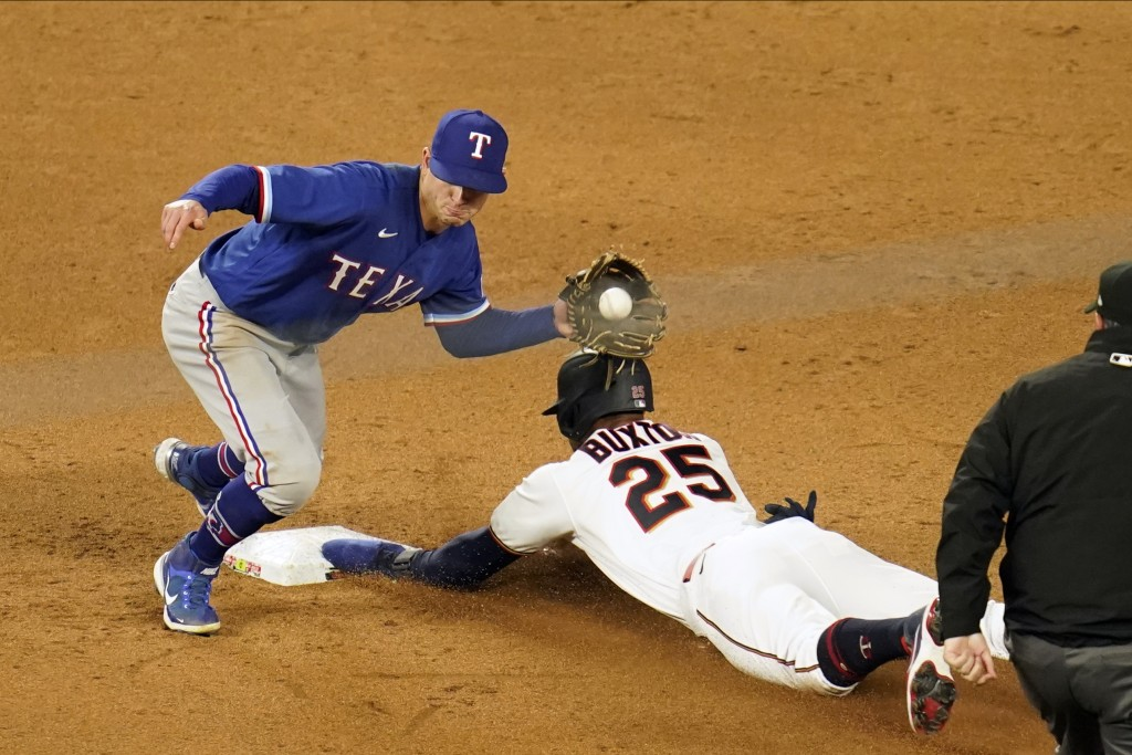 Minnesota Twins' Byron Buxton, right, beats the throw to Texas Rangers second baseman Nick Solak, left, as he steals second base in the sixth inning o...