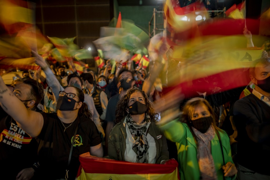 People wave Spanish flags as they react outside the Vox party headquarters in Madrid, Spain, Tuesday, May 4, 2021. Madrid residents voted in droves fo...
