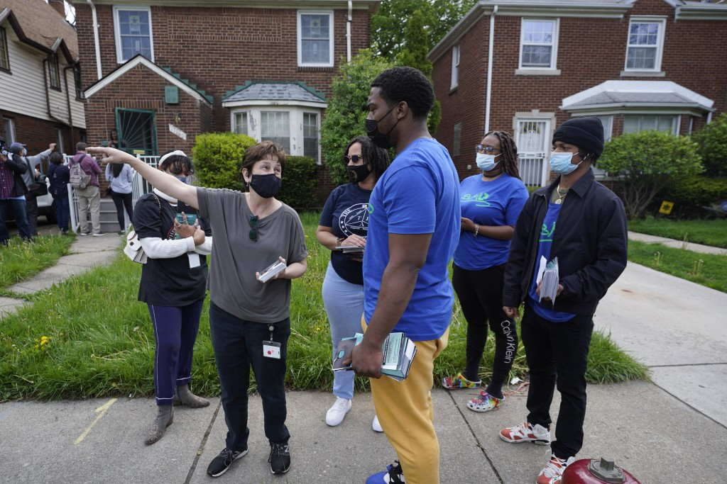 Volunteers meet before fanning out to place flyers on homes in Detroit, Tuesday, May 4, 2021. Officials are walking door-to-door to encourage resident...
