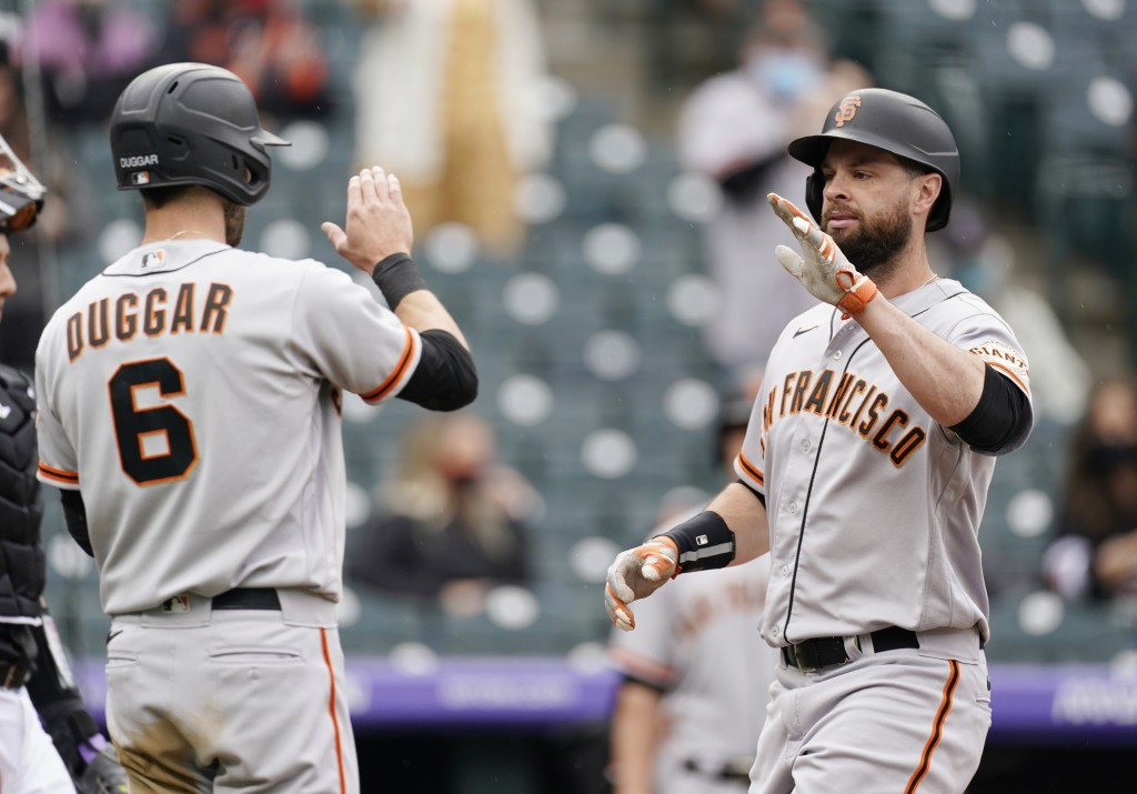 San Francisco Giants' Steven Duggar, left, waits to congratulate Brandon Belt as he crosses home plate after hitting a three-run home run in the first...