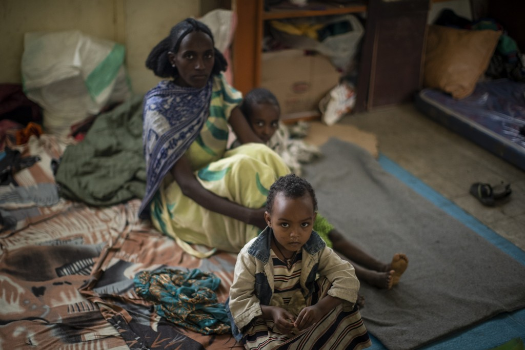 A displaced Tigrayan family sit in the classroom where they now live at the Hadnet General Secondary School which has become a makeshift home to thous...