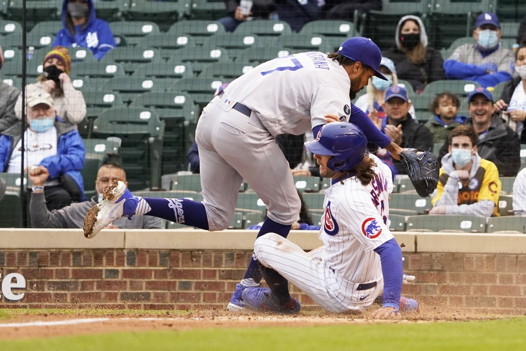 Chicago Cubs' Jake Marisnick, right, slides safely into home plate as Los Angeles Dodgers relief pitcher Dennis Santana (77) tries to make a tag durin...