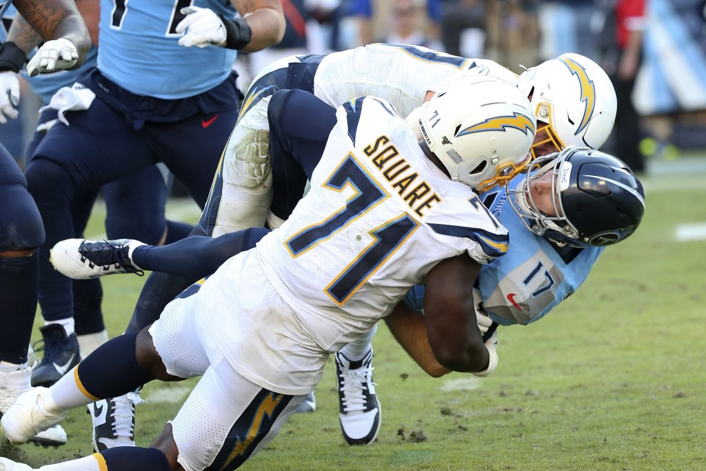 FILE - Tennessee Titans quarterback Ryan Tannehill (17) is sacked and fumbles from hits by Los Angeles Chargers defenders Joey Bosa and Damion Square ...