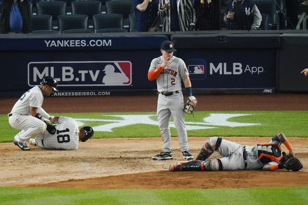 Houston Astros' Alex Bregman, center, watches as New York Yankees' Rougned Odor, left, and Houston Astros catcher Martin Maldonado, right, react to be...