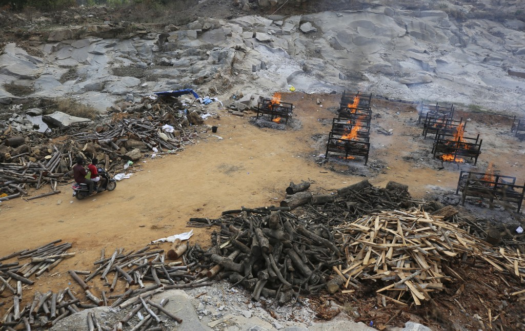 Workers arrive with a container of fuel as funeral pyres of COVID-19 victims burn at an open crematorium set up at a granite quarry on the outskirts o...