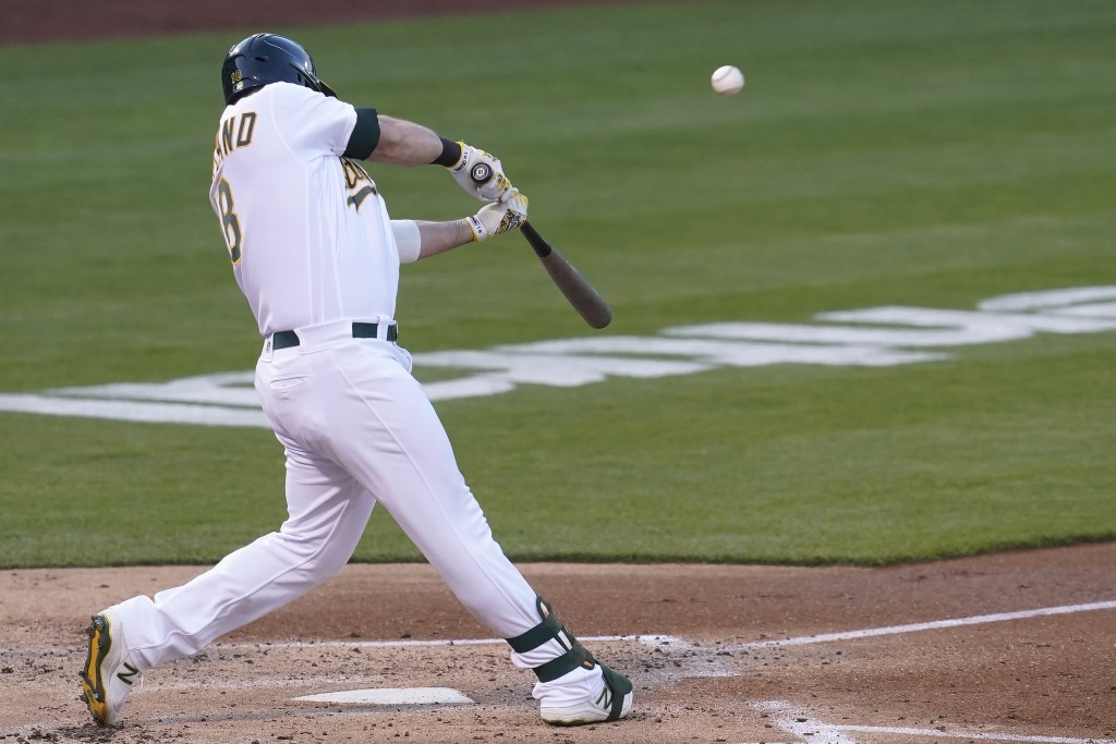 Oakland Athletics' Mitch Moreland hits a two-run home run against the Toronto Blue Jays during the second inning of a baseball game in Oakland, Calif....