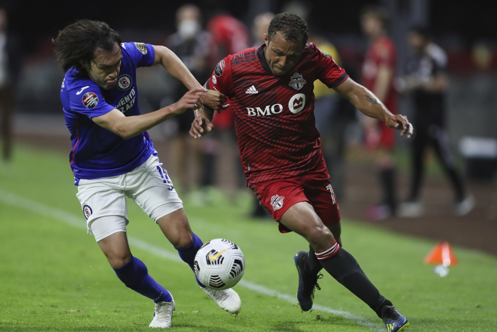 Jose Martinez of Mexico's Cruz Azul, left, challenges Jahkeele Marshall-Rutty of Canada's Toronto FC during a CONCACAF Champions League quarterfinal s...