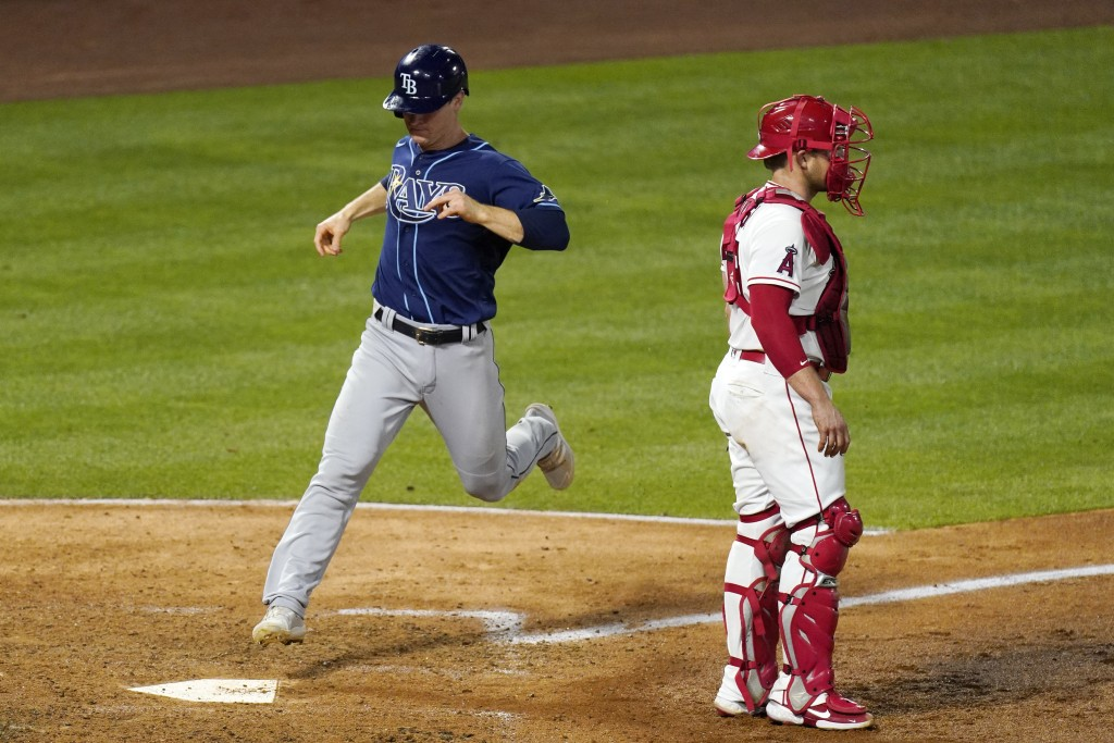 Tampa Bay Rays' Joey Wendle, left, scores on a double by Kevin Kiermaier as Los Angeles Angels catcher Max Stassi stands at the plate during the sixth...