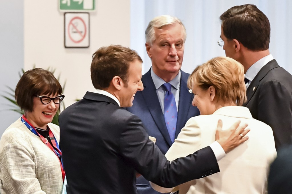 FILE - In this Friday, Oct. 20, 2017 file photo, French President Emmanuel Macron, second left, speaks with German Chancellor Angela Merkel, second ri...