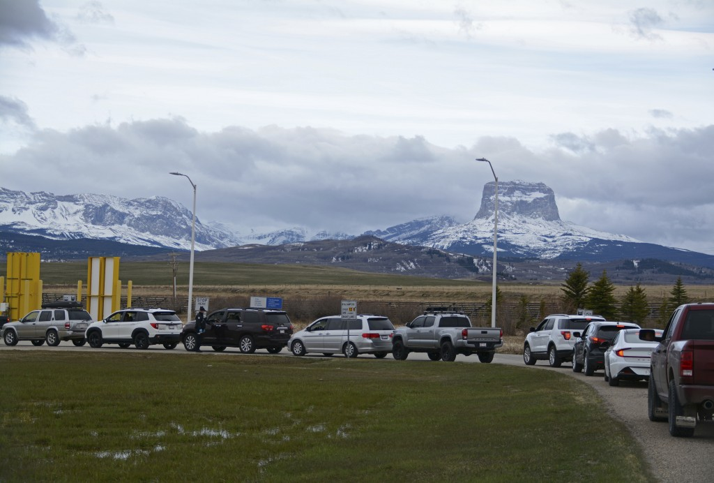 In this Thursday, April 29, 2021, photo, Canadians drive-in at the Piegan-Carway border to receive a COVID-19 from the Blackfeet tribe near Babb, Mont...