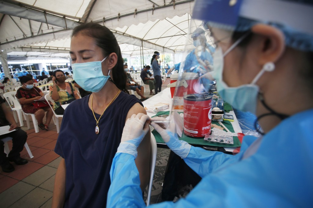 In this Tuesday, May 4, 2021, photo, a health worker administers a dose of the Sinovac COVID-19 vaccine to residents of the Klong Toey area, a neighbo...