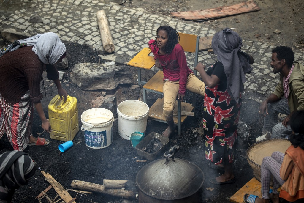 """A displaced Tigrayan girl sits on a school chair as women prepare """"Injera"""" flatbread in the courtyard of the Hadnet General Secondary School which has..."""