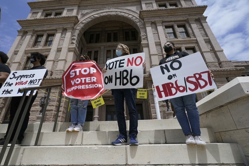 FILE - In this April 21, 2021, file photo, people opposed to Texas voter bills HB6 and SB7 hold signs during a news conference hosted by Texas Rising ...