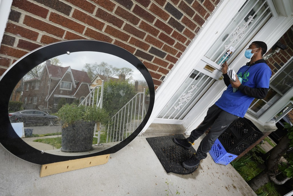 Sirgregory Allen leaves a flyer at a home in Detroit, Tuesday, May 4, 2021. Officials are walking door-to-door to encourage residents of the majority ...