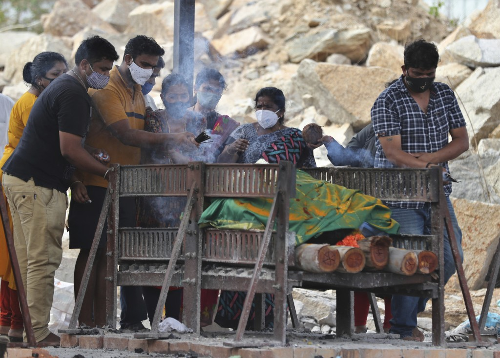 Family members perform last rites of a COVID-19 victim at an open crematorium set up at a granite quarry on the outskirts of Bengaluru, India, Wednesd...