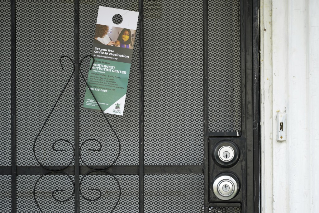 A flyer is shown left on a home in Detroit, Tuesday, May 4, 2021. Officials are walking door-to-door to encourage residents of the majority Black city...
