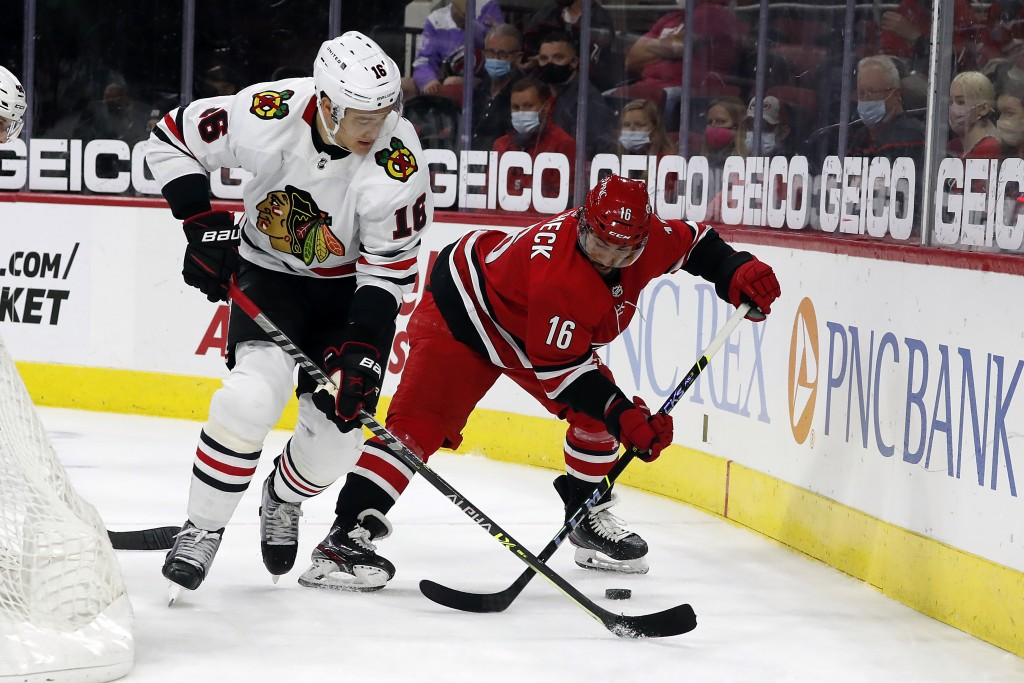 Carolina Hurricanes' Vincent Trocheck (16) is pestered by Chicago Blackhawks' Nikita Zadorov (16) behind the net during the second period of an NHL ho...