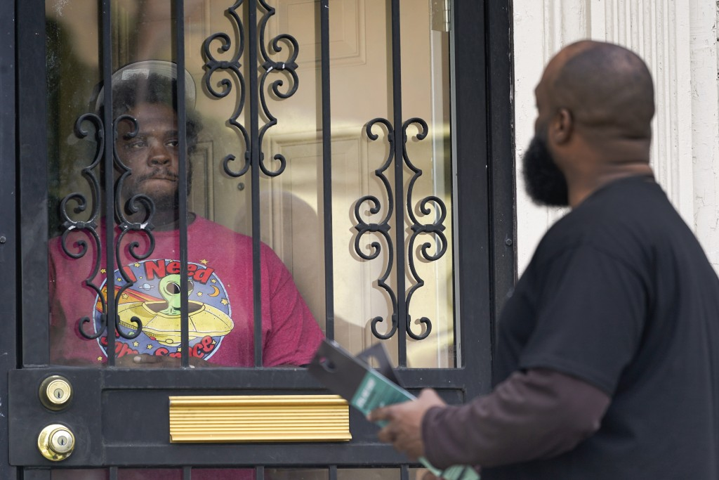 Anthony Brinson, right, talks with a resident while leaving a flyer at a home in Detroit, Tuesday, May 4, 2021. Officials are walking door-to-door to ...