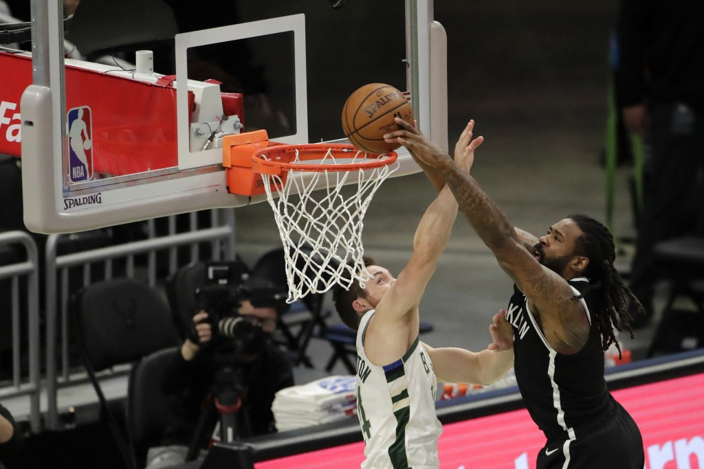 Brooklyn Nets' DeAndre Jordan is fouled by Milwaukee Bucks' Pat Connaughton as he attempts a shot during the first half of an NBA basketball game Tues...