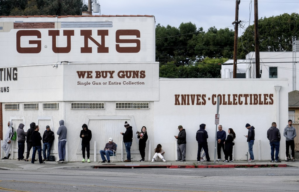 FILE - In this Sunday, March 15, 2020, file photo, people wait in line to enter a gun store in Culver City, Calif. After a year of pandemic lockdowns,...