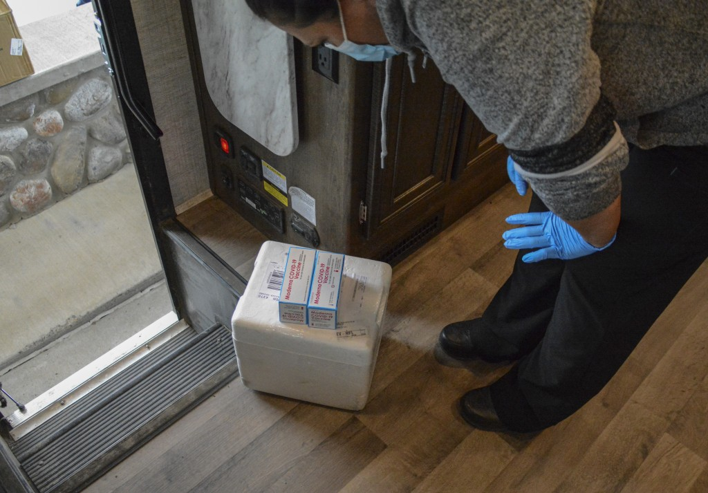 In this Thursday, April 29, 2021, photo, a Blackfeet tribe nurse examines a delivery of Moderna and Pfizer COVID-19 vaccines that will be given to Can...