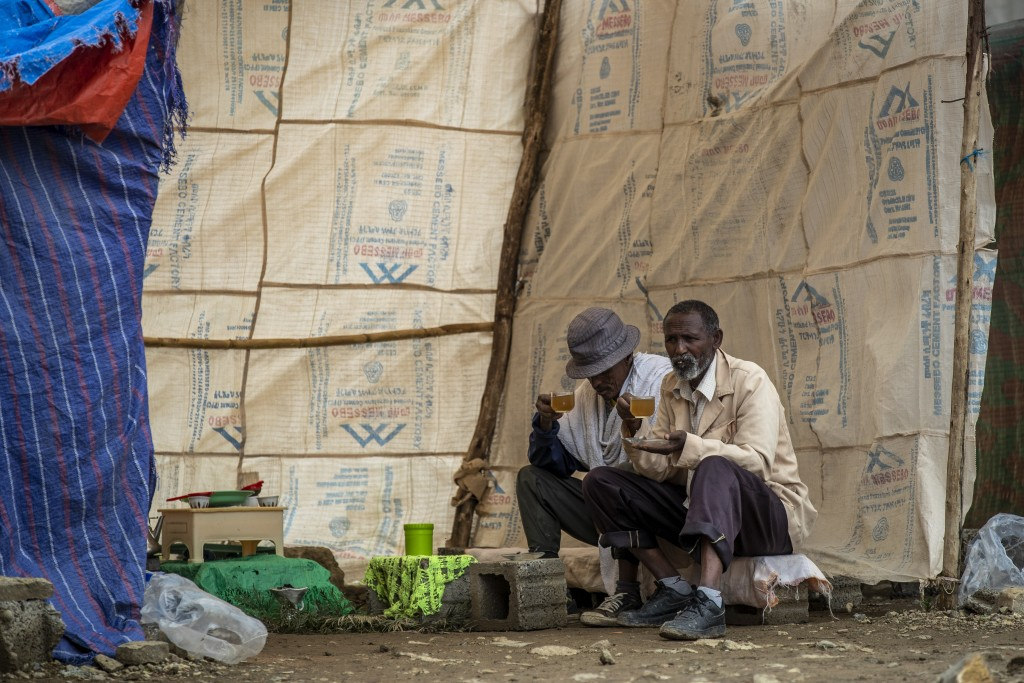 Displaced Tigrayan men drink tea outside the Hadnet General Secondary School which has become a makeshift home to thousands displaced by the conflict,...