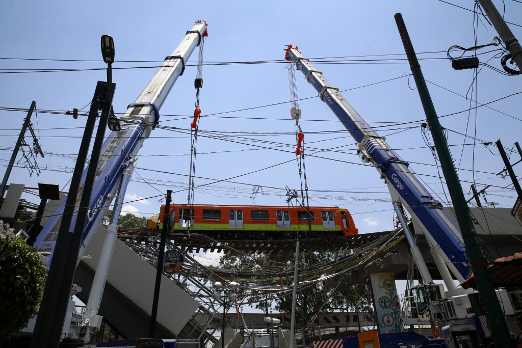 A subway car is prepared to be lowered to the ground, with the help of cranes, from a collapsed elevated section of the metro, in Mexico City, Tuesday...