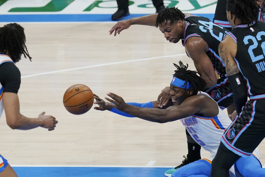 Oklahoma City Thunder forward Luguentz Dort (5) passes in front of Sacramento Kings guard Buddy Hield (24) in the first half of an NBA basketball game...
