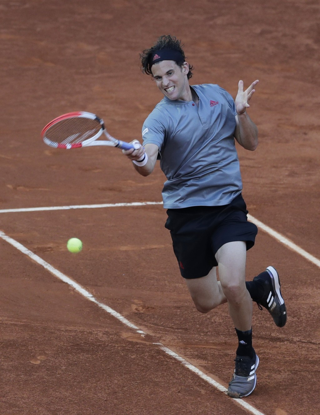 Dominic Thiem of Austria returns the ball to Marcos Giron of the U.S. during their match at the Madrid Open tennis tournament in Madrid, Spain, Tuesda...