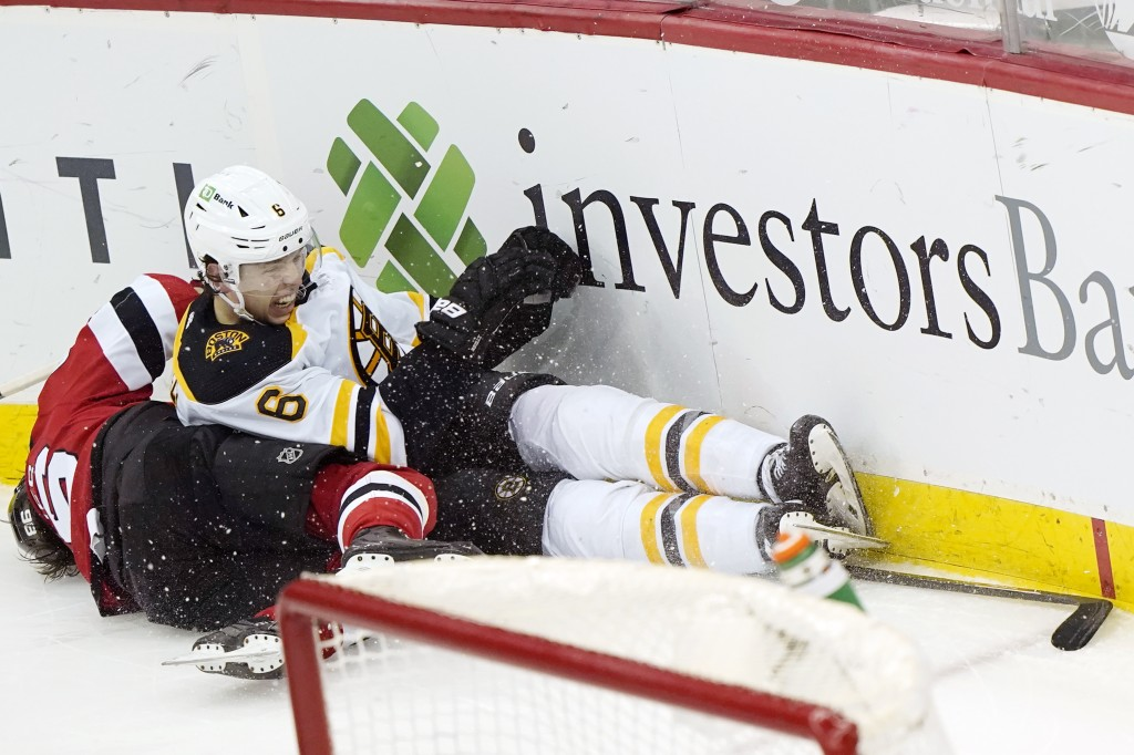 Boston Bruins defenseman Mike Reilly (6) and New Jersey Devils center Jack Hughes (86) collide against the boards behind the Bruins net during the sec...
