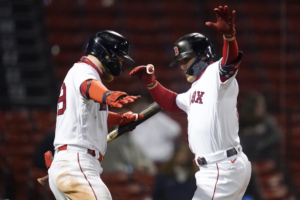 Boston Red Sox's Enrique Hernandez, right, dances with Alex Verdugo after crossing home plate while celebrating his solo home run during the eighth in...