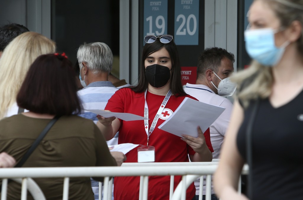 A Red Cross volunteer hands people papers before entering the COVID-19 vaccination center, at A1 Arena in Skopje, North Macedonia, on Tuesday, May 4, ...