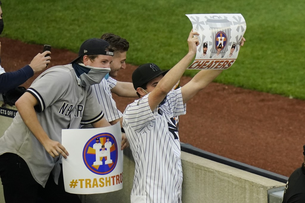 New York Yankees fans hold signs before the start of a baseball game between the New York Yankees and the Houston Astros Tuesday, May 4, 2021, in New ...