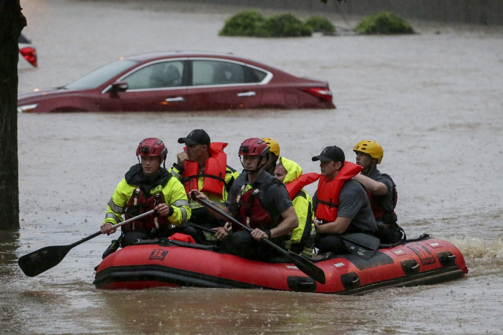 Residents of the Crescent at Lakeshore apartment complex are rescued by Homewood Fire and Rescue as severe weather produced torrential rainfall floodi...