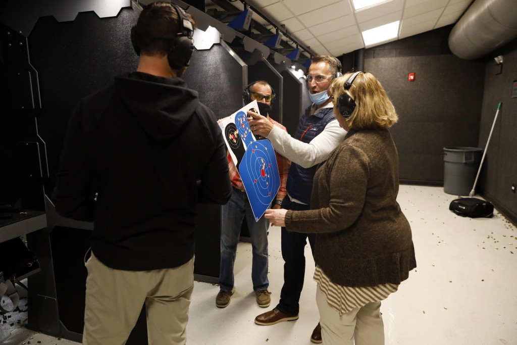 Chicago resident Ray Mandel, center, shows his target to others during a shooting session at Maxon Shooter's Supplies and Indoor Range, Friday, April ...
