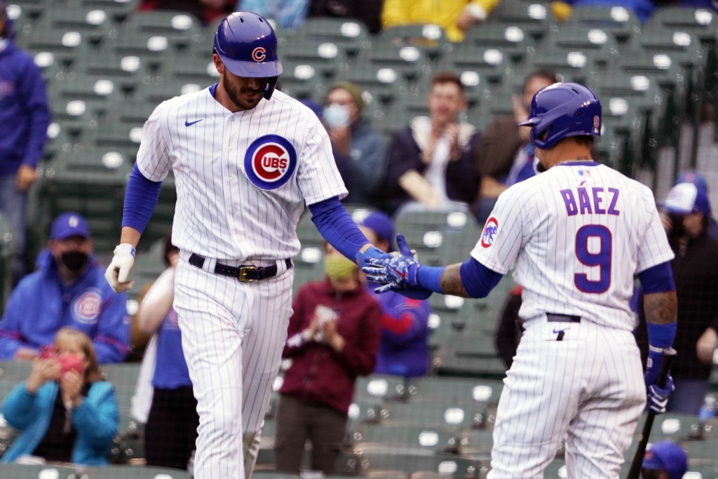 Chicago Cubs' Kris Bryant, left, is greeted by Javier Baez (9) after scoring against the Los Angeles Dodgers during the first inning of the first base...