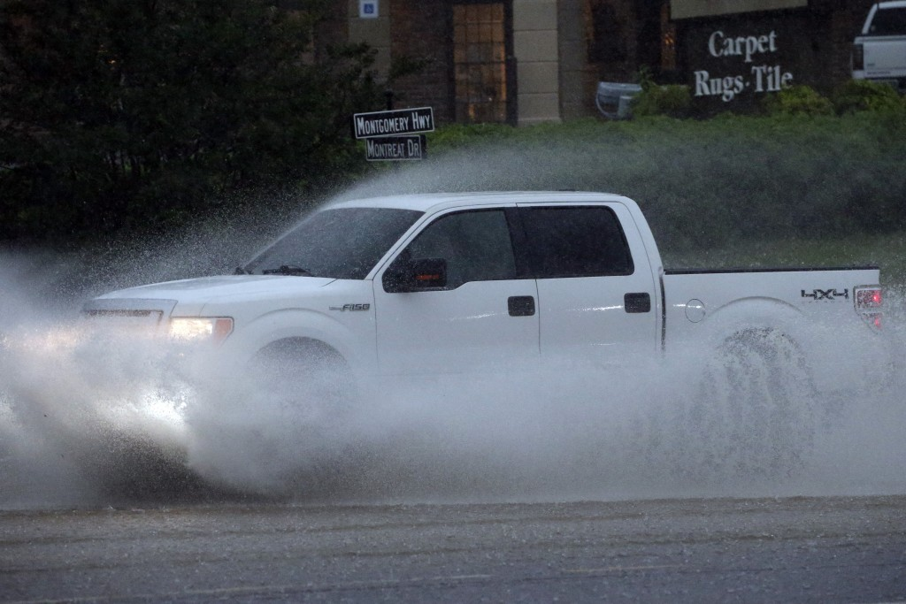 A pickup truck travels along a flooded road as severe weather produces torrential rainfall, Tuesday, May 4, 2021 in Vestavia, Ala. (AP Photo/Butch Dil...