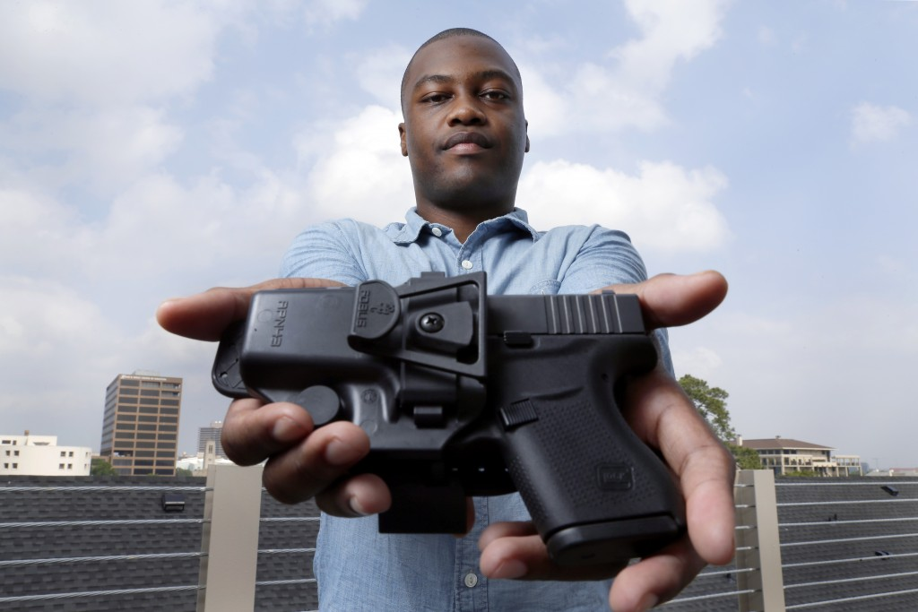 Charles Blain, a new gun owner, poses with his holstered 9mm Glock 43 handgun, Monday, May 3, 2021, on the parking garage of his apartment complex in ...