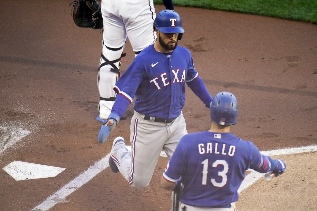 Texas Rangers' Isiah Kiner-Falefa, left, is greeted by Joey Gallo as he scores on a hit by Adolis Garcia in the first inning of a baseball game agains...