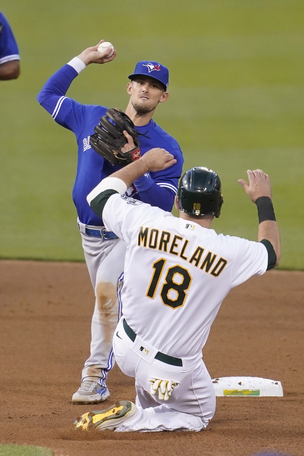 Toronto Blue Jays' Cavan Biggio, top, throws to first base after forcing Oakland Athletics' Mitch Moreland (18) out at second base on a double play hi...