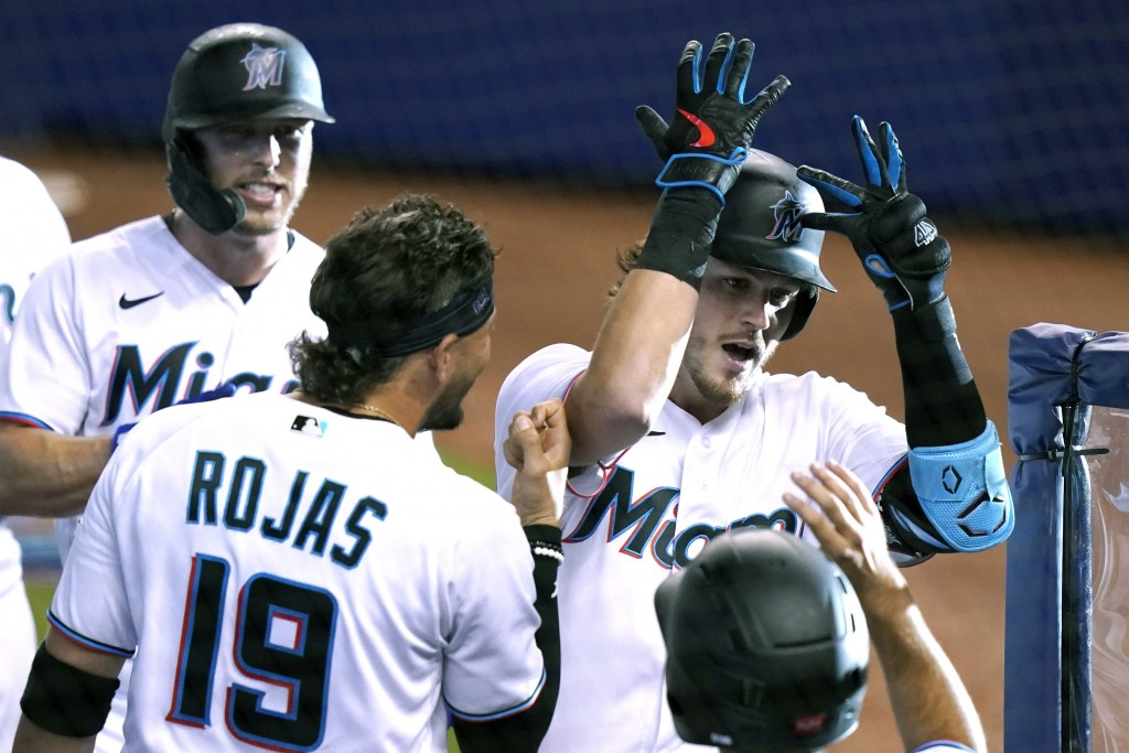 Miami Marlins' Brian Anderson (15) celebrates with Miguel Rojas (19) after hitting a three-run home run during the first inning of a baseball game aga...
