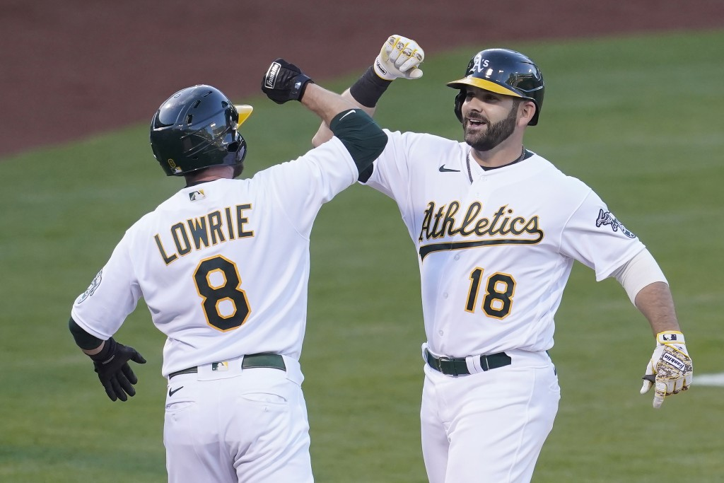 Oakland Athletics' Mitch Moreland (18) celebrates after hitting a two-run home run that scored Jed Lowrie (8) during the second inning of a baseball g...