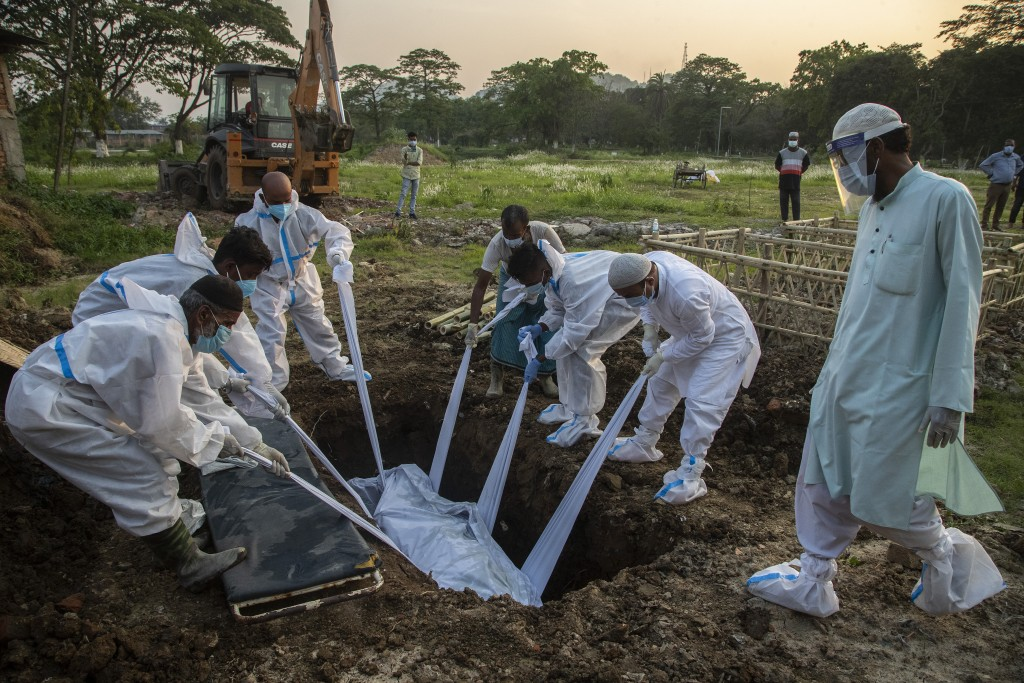 FILE - In this April 25, 2021, file photo, relatives and municipal workers in protective suit bury a COVID-19 victim in Gauhati, India. Despite clear ...
