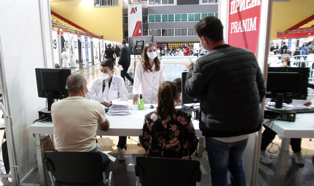 People talk to health workers prior to their vaccination at the center for mass vaccination against COVID-19, at A1 Arena in Skopje, North Macedonia, ...