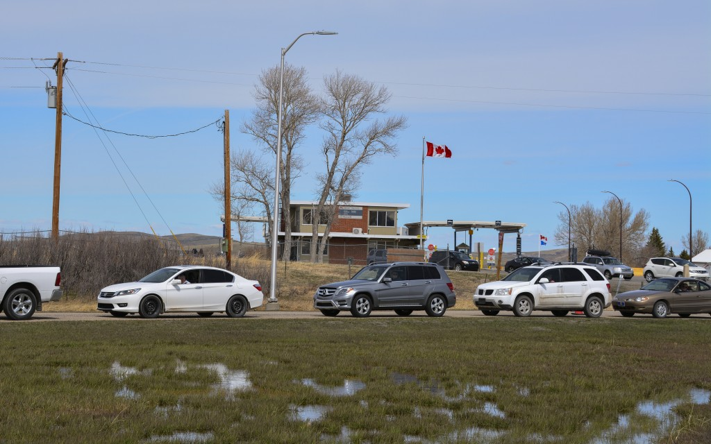 In this Wednesday, April 28, 2021, photo, cars line up at the Piegan-Carway border crossing between Montana and Canada, near Babb, Mont. The Blackfeet...