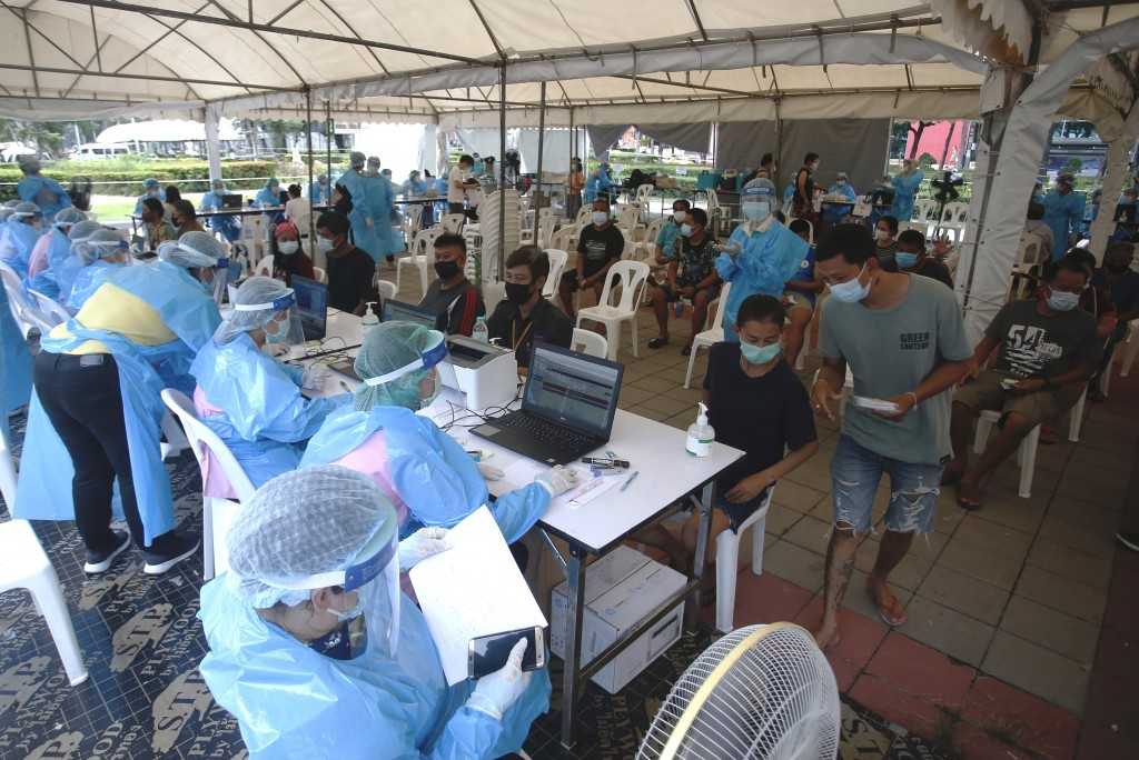 In this Tuesday, May 4, 2021, photo, residents of the Klong Toey neighborhood, an area with a current spike in coronavirus cases, wait to receive the ...