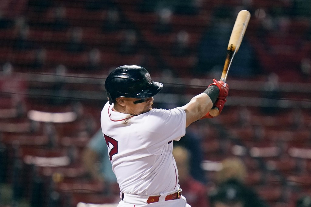 Boston Red Sox's Christian Vazquez follows through on his RBI double during the sixth inning of a baseball game against the Detroit Tigers at Fenway P...