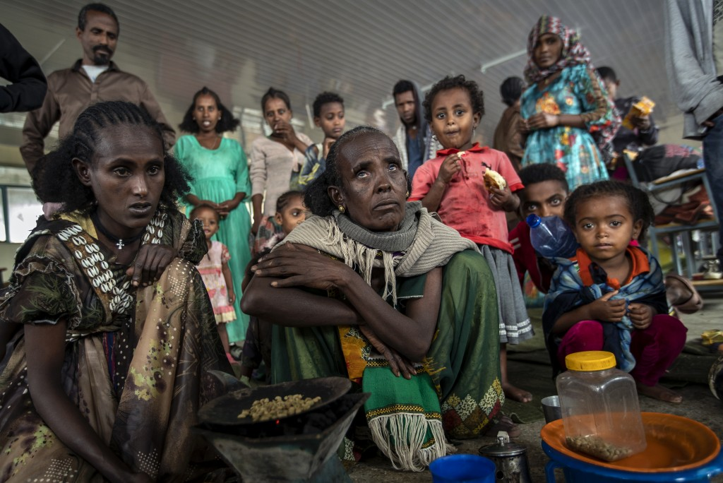 Displaced Tigrayan women Tarik, 60, center, and Meresaeta, left, who fled from the town of Samre, roast coffee beans over a wood stove in the classroo...
