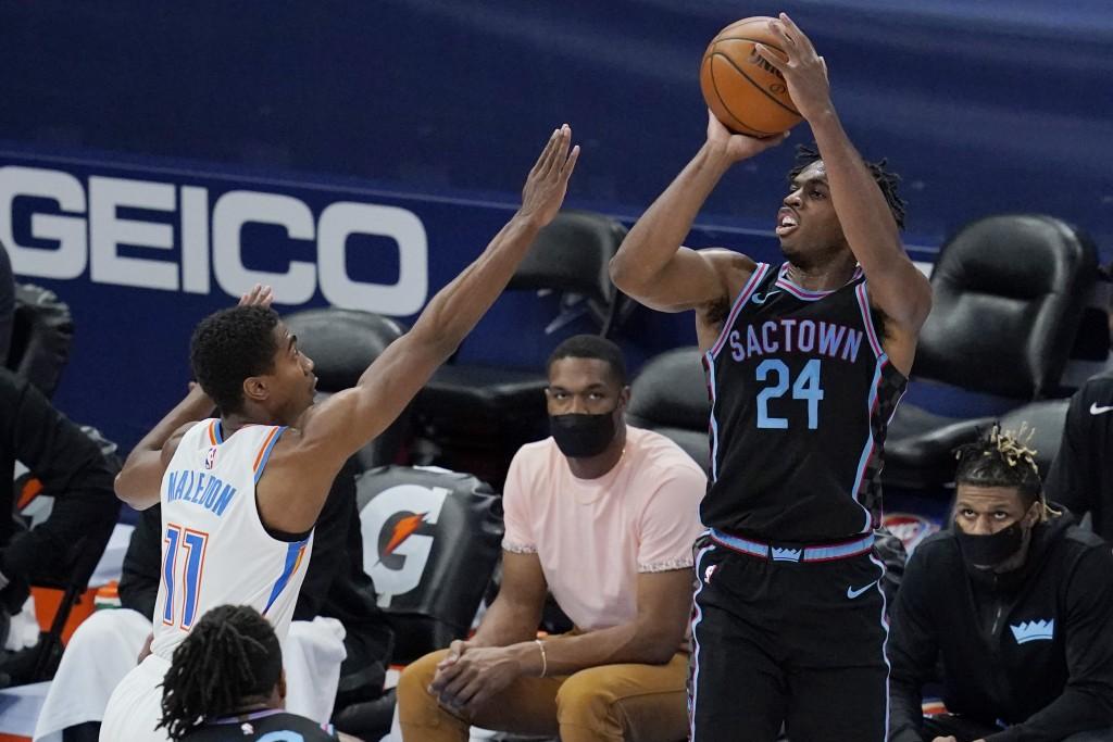 Sacramento Kings guard Buddy Hield (24) shoots over Oklahoma City Thunder guard Theo Maledon (11) in the first half of an NBA basketball game Tuesday,...